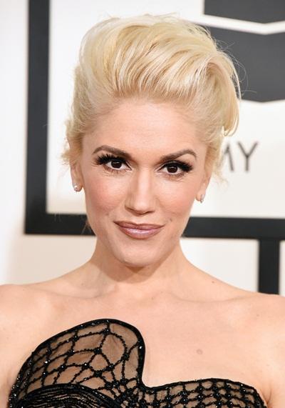 Mái tóc của Gwen Stefani được bới cao và chải rối phồng phía trước, phù hợp với kiểu trang điểm mặt đầy cá tính.