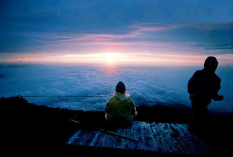 Tác giả Trung Nghĩa ngồi trên đỉnh phú Sĩ (Nhật Bản) ngắm mặt trời mọc sau chuyến leo lên ngọn núi nổi tiếng này.