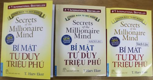 """""""Bí mật tư duy triệu phú"""" bản thật (bên trái) được in với chất lượng in và giấy cao cấp hơn nhưng lại có giá bán thấp hơn sách in lậu (hai cuốn bên phải)."""