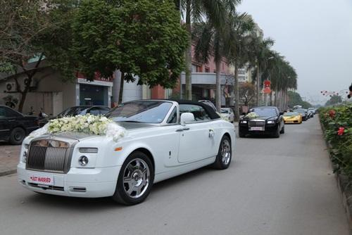 Cặp tân lang, tân nương ngồi trên xe Rolls-Royce Phantom mui trần 2 cửa màu trắng.