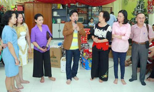 Khánh Ly và ca sĩ Quang Thành (thứ ba, thứ tư từ trái qua) đến thăm một trung tâm trẻ mồ côi, khuyết tật ở Hà Nội.