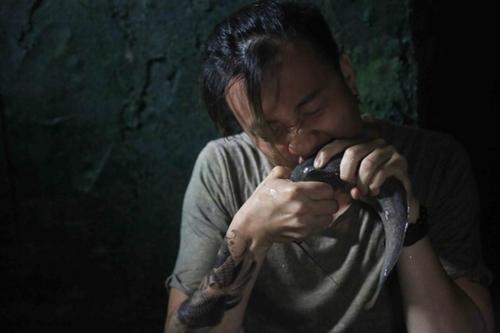 Nhân vật chính ăn cá trê sống trong phim. Ảnh: ĐPCC.
