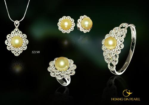 Bộ trang sức Nữ hoàng của biển sử dụng những viên ngọc trai South Sea bóng tròn, có ánh sắc vàng kim đặc trưng nổi bật, kích thước ngọc 12,1-12,5 mm đi cùng thiết kế dáng hoa xếp từng cánh mỏng mềm mại và tinh xảo. Giá tham khảo của bộ trang sức là 500 triệu đồng.