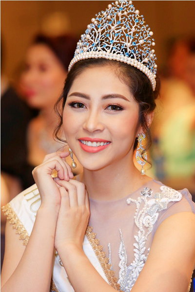Hoa hậu Đại Dương 2014 Đặng Thu Thảo xuất hiện với chiếc vương miện thiết kế từ nhiều viên ngọc trai trắng đính đá quý màu xanh. Người đẹp sử dụng khuyên tai ngọc trai nổi bật tạo điểm nhấn thu hút.