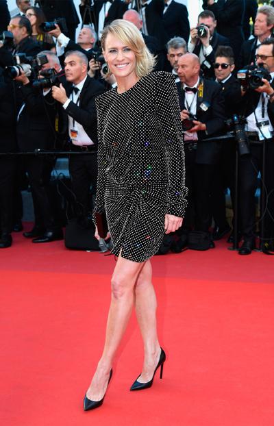 Nữ diễn viên kỳ cựu Robin Wright cuốn hút với chiếc đầm đơn giản nhưng ấn tượng từ bộ sưu tập thu đông 2017 của Saint Laurent. Cô hoàn thiện vẻ ngoài với giày cao gót da màu đen của thương hiệu. Stylist Kemal Harris, người tạo dựng phong cách cho Robin Wright tại Cannes đã thuyết phục nữ diễn viên lựa chọn trang phục mini dress lấp lánh và trẻ trung thiết kế bởi Anthony Vaccarello.