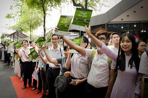 Các độc giả trẻ giơ cao cuốn photo-book về bộ phim chuyển thể sắp ra mắt.