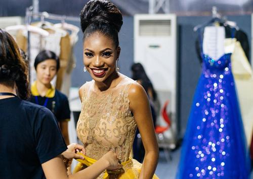 Hoa hậu Nigeria được giúp đỡ mặc trang phục dạ hội.