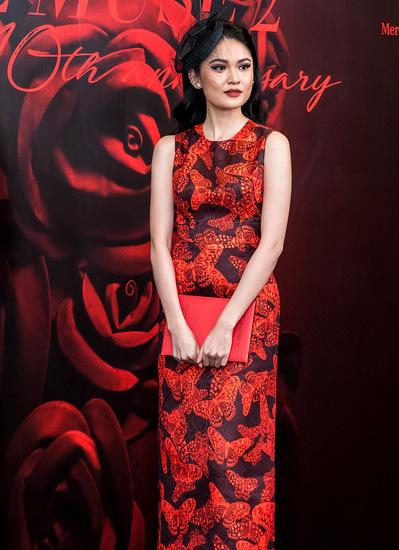 Á hậu Việt Nam 2016 Thuỳ Dung thanh lịch với đầm bodycon hoạ tiết cánh bướm. Người đẹp kết hợp trang phục cùng nơ lưới màu đen, giày cao gót đỏ thanh mảnh, đồng điệu với trang phục.