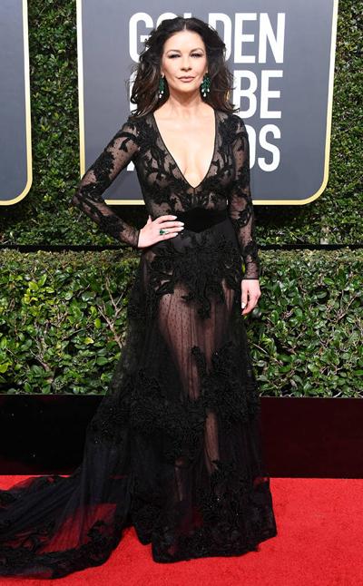 Trước đó, khi xuất hiện trên thảm đỏ, Catherine Zeta-Jones tạo dáng với chiếc váy ren xuyên thấu màu đen.