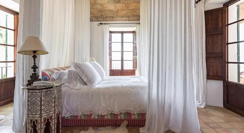 Phòng ngủ không kê nhiều đồ đạc, nhấn giữa nhà với màn và ga trải tông trắng.