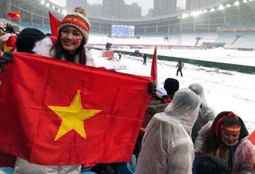 Á hậu Thanh Tú đang có mặt tại Thường Châu. Người đẹp một tay cầm cờ đỏ sao vàng, một tay cầm ô vì trời đang mưa nặng hạt.