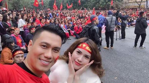 Diễn viên Việt Anh (trái) và bà xã Hương Trần cổ vũ U23 Việt Nam cùng sinh viên Đại học Kinh tế Quốc dân ở Hà Nội.