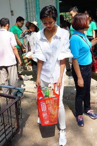 Cô ôm đỡ phần quà nặng ra xe cho một cụ già yếu sức. Vài bạn trẻ địa phương ngỏ lời chụp selfie nhưng HHen Niê hẹn dịp khác vì bận lo cho người bệnh.