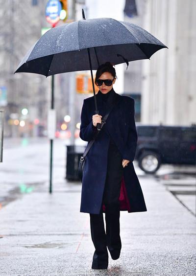 Trước đó, cô tới show thời trang một mình, mặc áo khoác màu xanh thẫm và che ô cùng tông trang phục.