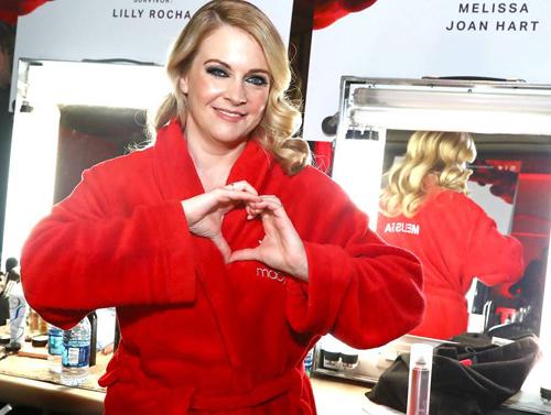 Phù thủy Melissa Joan Hart tạo hình trái tim, mặc trang phục màu đỏ ở hậu trường buổi trình diễn thời trang Go Red for Women Red Dress Collection.