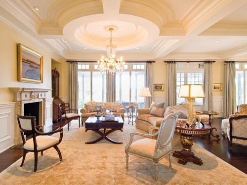 Phòng khách lớn được trang trí hai lò sưởi, nội thất đóng bằng gỗ óc chó màu Bordeaux.
