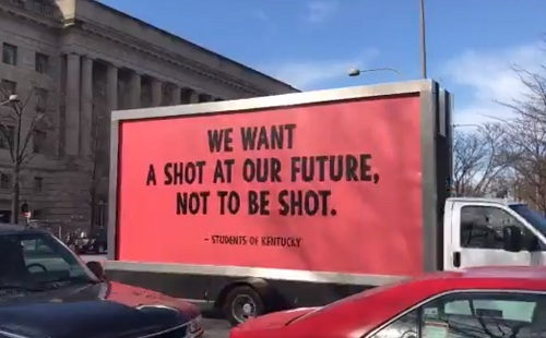 Một chiếc xe chở tấm biển phản đối súng.