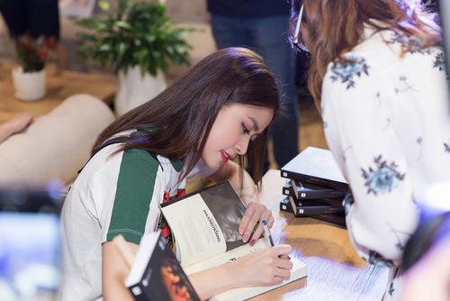 Ca sĩ nắn nót ký tặng sách cho độc giả.