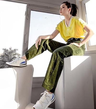 Lần khác, nữ ca sĩ toát lên tinh thần trẻ trung với áo phông và quần nhung tăm ống suông. Việcchọn giày có phần xanh dương ở gót đi kèm quần xanh lục khiến cho sự kết hợp trở nên thú vị. Thắt lưng đục lỗ ăn ý với khuyên tai tròn lớn, thể hiện sự tinh tế của người mặc.
