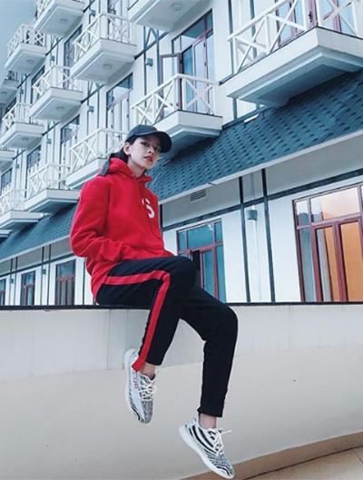 Thể hiện sự mạnh mẽ, Chi Pu chọn áo hoodie màu đỏ ăn ý với đường kẻ sọc của quần ống côn. Chiếc giày trắng vằn vện trở thành điểm nhấn cho bộ cánh, tạo thành cuộc chơi của bộ ba sắc màu kinh điển: trắng - đen - đỏ.