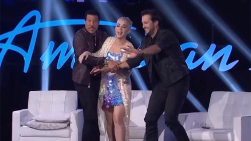 Lionel Richie (trái) và Luke Bryan (phải) cố giữ Katy Perry khỏi hành động quá khích.