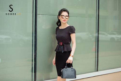 Trong các mẫu xuân hè mới mà doanh nhân Hà Bùi chọn lựa để thực hiện bộ ảnh streetstyle, các thiết kế áo cổ tròn được chị yêu thích hơn cả. Khi mix cùng chân váy bút chì màu đen, chị phối hợp với áo kẻ dọc màu trầm có nơ điệu đà thắt ở eo. Set đồ này góp phần làm toát lên phong thái tự tin của một nữdoanh nhân thành đạt.