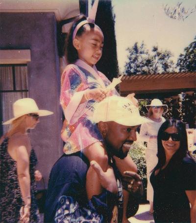 Kim Kardashian chia sẻ ảnh Kanye West đang kiệu con gái North West: Chúc mừng Ngày của Cha, anh yêu! Cảm ơn anh đã trở thành người bố tốt của các con.