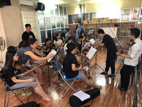 Nhạc trưởng Lê Quang Minh (áo đen, phải) hướng dẫn các nhạc công nhí tập luyện.