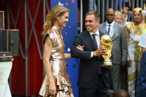 Siêu mẫu NgaNatalia Vodianova (trái) tiến ra sân khấu cùng cựuđội trưởng tuyển Đức vô địch World Cup 2014 -Philipp Lahm. Hai người mang theo chiếc cúp vàng của giải đấu năm nay.