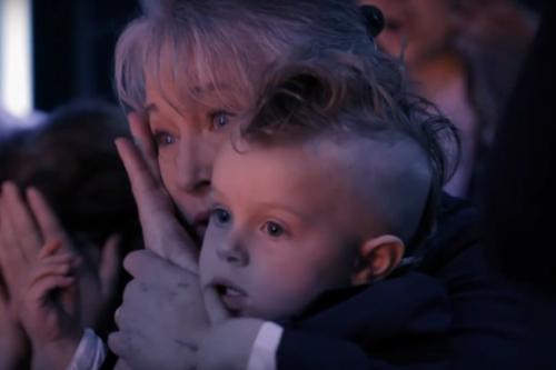 Mẹ của Mary bế con trai 2 tuổi của cặp vợ chồng ngồi ở hàng ghế khán giả.