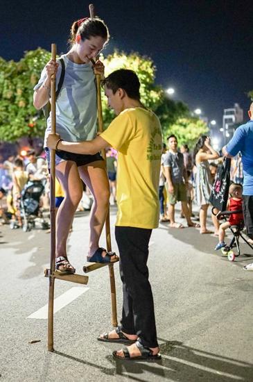 Trò đi cà kheo hấp dẫn người dân tại phố đi bộ.