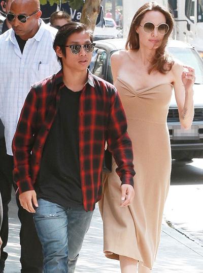 Pax Thiên mặc áo kẻ đỏ đen, đeo kính râm phong cách. Con nuôi 14 tuổi của Angelina Jolie cao gần bằng mẹ.