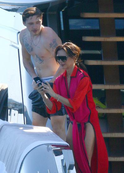 Victoria Beckham mặc bikini màu xám, bên ngoài choàng áo đỏ. Nhà thiết kế không xuống nước mà ở trên dùng điện thoại ghi lại khoảnh khắc vui đùa của chồng con.
