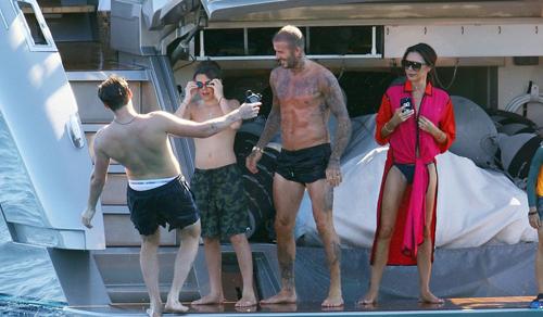 Ba bố con Beckham chuẩn bị nhảy nước, trong khi Victoria sẵn sàng cầm điện thoại chụp ảnh.