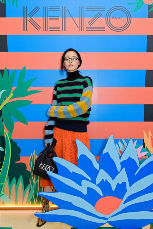 Hình ảnh rừng nhiệt đới thường xuyên được lấy làm nguồn cảm hứng cho các BST của Takada Kenzo. Là khách mời của thương hiệu,Khánh Linh The Face chọn chiếc áo len kẻ nhiều màu sắc phối cùng chân váy cam thuộc bộ sưu tập. Cô hoàn thiện set đồ với đôi boot họa tiết da trăn và túi xách Kenzo.