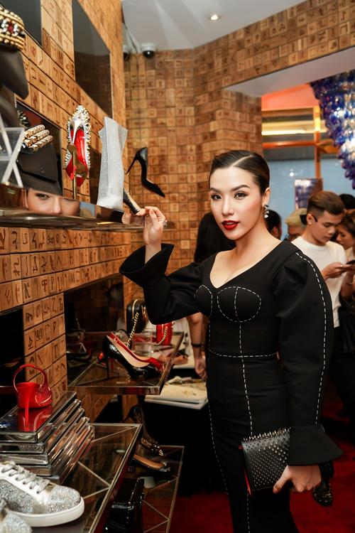 Á hậu Khánh Phương diện cây đồ đen phong cách black-on-black. Cô thích thú trước thiết kế giày cao gót nạm đá quý trong bộ sưu tập vừa ra mắt của thương hiệu.