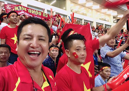 Nghệ sĩ Chí Trung (trái) cổ vũ đội tuyển Việt Nam ở sân vận động quốc gia Mỹ Đình (Hà Nội).