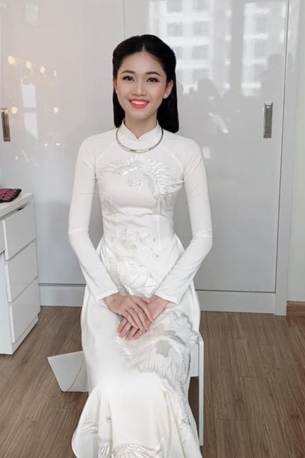 Á hậu Thanh Tú diện áo dài trắng, đeo vòng kiềng và làm tóc kiểu thiếu nữ Hà Nội xưa.