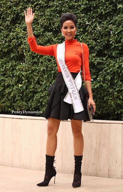 Cô gái Ê đê chọn phong cách năng động trong chiếc áo cổ lọ màu đỏ cam và chân váy chữ A xếp bèo, bốt tất.