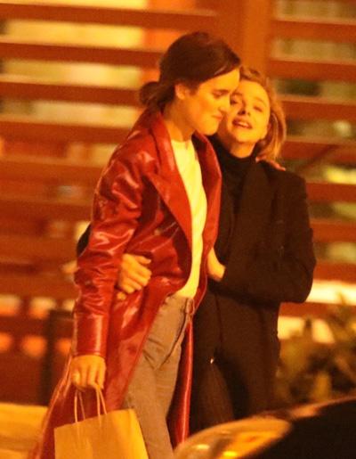 Cả hai mặc áo khoác dáng dài, vừa đi vừa cười nói và có những cử chỉ ôm ấp, gần gũi.
