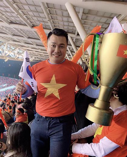 Lý Hùng cầm chiếc cúp vàng ăn mừng trên khán đài sân Mỹ Đình.