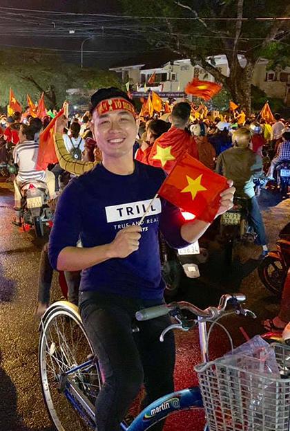 Đang có chuyến công tác ở Hội An, Nguyên Khang đạp xe cùng người dân ở đây, vẫy cờ chúc mừng đội tuyển.