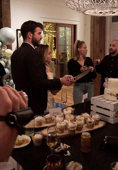 Miley Cyrus và Liam Hemsworth nắm tay nhau cầm dao cắt bánh. Mẹ cô đứng phía xa.