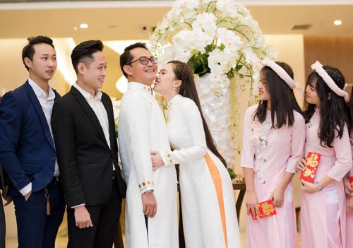 Cô dâu, chú rể diện áo dài trắng thêu nổi, vui vẻ cười đùa bên dàn phù dâu, phù rể.