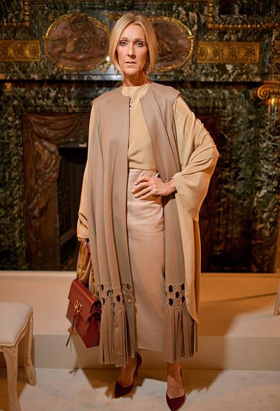 Ca sĩ 50 tuổi mặc váy dài màu be, kết hợp cùng khăn màu cát cháy và giày màu mận.