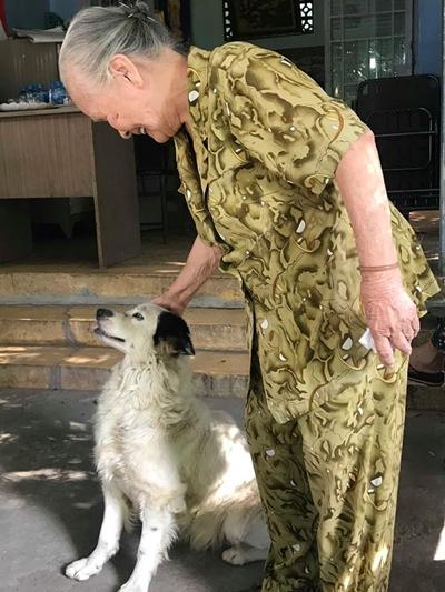 Ngọc Đáng bên chú chó nuôi trong Viện dưỡng lão.