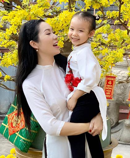 Mẹ con á hậu Trịnh Kim Chi đầu tư trang phục chụp ở góc sân có bối cảnh ngày Tết.