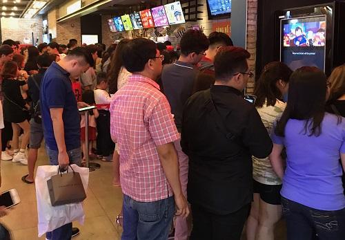Nhiều khán giả xếp hàng trước quầy bán vé và máylấy vé online ở một rạp tại TP HCM.