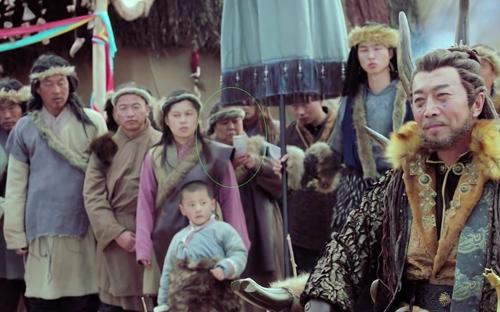 Một diễn viên quần chúng sử dụng điện thoại trong Đông cung.