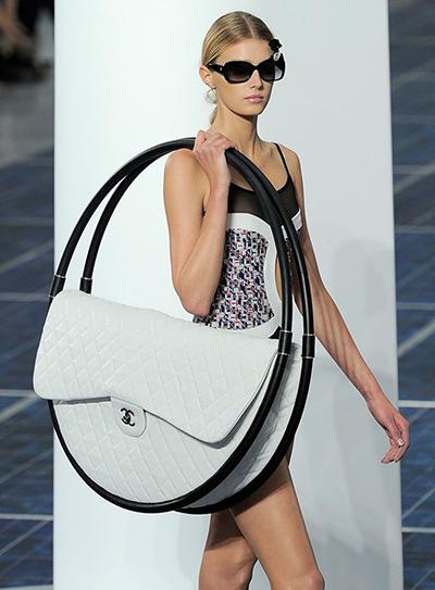 Chiếc túi Chanel kinh điển 2.55 lần nữa xuất hiện trong kiểu dáng biến tấu không ngừng sáng tạo qua từng năm, nhưng bất ngờ và đáng nhớ nhất vẫn là phiên bản 2013. Với phần nắp túi đặc trưng, phần quai túi được biến tấu ngộ nghĩnh như một chiếc vòng lớn, khiến giới mộ điệu tham gia buổi trình diễn SS13 không thể rời mắt.